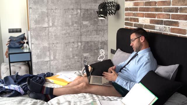 4k video geschäftsmann in unterhosen arbeiten zu hause und mit einem telekonferenzanruf aus seinem schlafzimmer - unterwäsche stock-videos und b-roll-filmmaterial