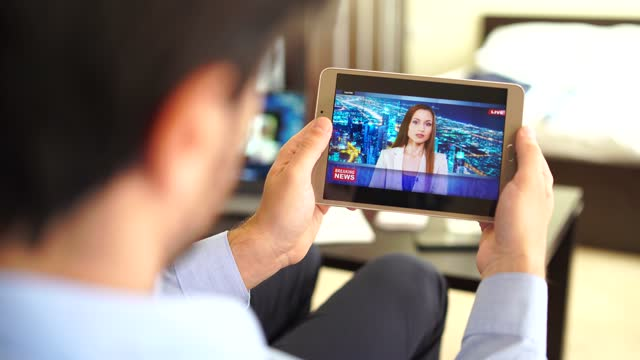 4k video businessman watching tv news on tablet  in hotel room tablet with screen showing online news - finance and economy stock videos & royalty-free footage