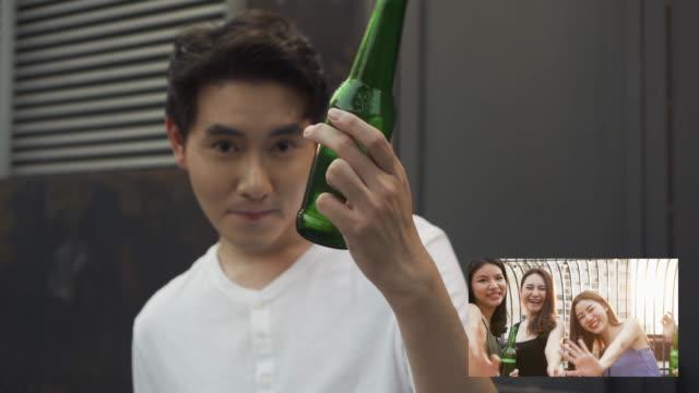vidéos et rushes de appel vidéo groupe d'amis asiatiques célébrant la fête et buvant de la bière ensemble - webcam