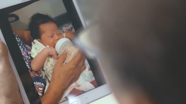 vídeos de stock, filmes e b-roll de chamada de vídeo : recém-nascido comendo bebê - câmara parada