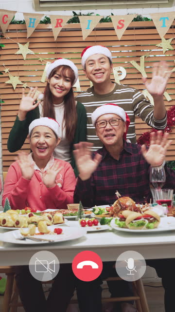 video call of a moment of southeast asian family, senior father, a mother with mid son and young wife, smiling, happiness around a lovely table on food dinner for christmas and cheering together to the celebration of december's holiday-decorated home. - 65 69 years stock videos & royalty-free footage