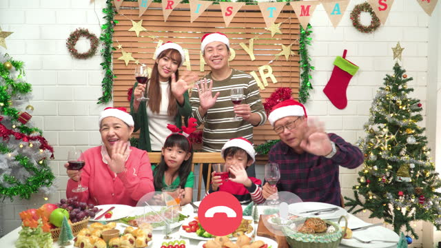 video call of a moment of southeast asian multi-generation family with smiling, happiness around a lovely table on food dinner for christmas and cheering together to the celebration of december's holiday-decorated home. - 65 69 years stock videos & royalty-free footage