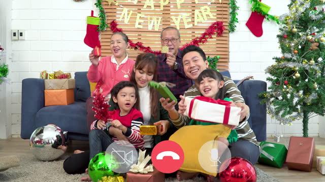 videoanrufansicht: südostasiatische mehrgenerationenfamilie lächelt und winkt in die kamera, um hallo freund zu sagen, wie online für den weihnachtstag übertragen. sohn und tochter fühlen sich aufregend mit weihnachtsgeschenk was ist das. - 35 39 years stock-videos und b-roll-filmmaterial