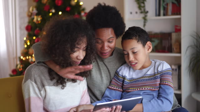video call with family on christmas day during pandemic - christmas tree stock videos & royalty-free footage