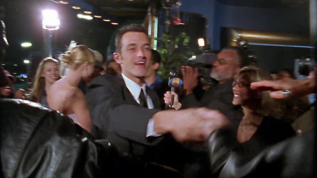Video camera point of view famous man moving through crowd of groupies and press / shaking hands