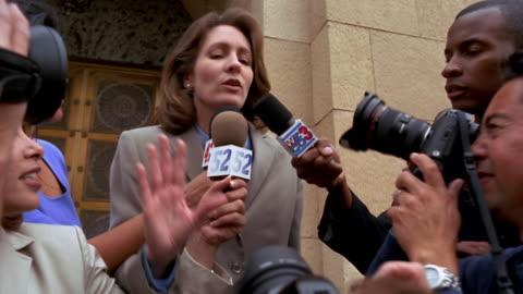 video camera point of view low angle medium shot woman in suit speaking / surrounded by press - journalist bildbanksvideor och videomaterial från bakom kulisserna
