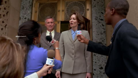 video camera point of view medium shot man and woman in suits exiting building / giving press conference - uomo politico video stock e b–roll