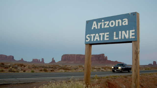 a video clip closeup of the arizona state line sign panning left to the view of monument valley - road sign stock videos & royalty-free footage
