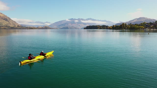 vídeos de stock e filmes b-roll de video clip drone flying over a beautiful lake by flying forward there is a reflection of water and a yellow canoe can be seen in the front on the front there is a snow-capped mountain, a concept of relaxation. natural travel - nova zelândia