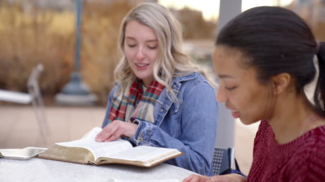 a video clip of a group of multiple race students having a discussion and studying the bible - bible stock videos & royalty-free footage