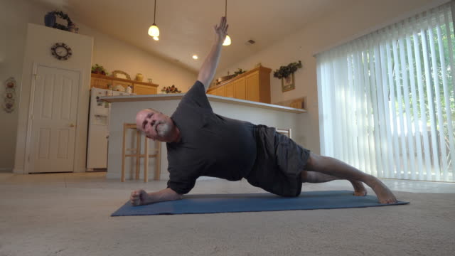 A Video Clip Of A Middle Aged Man Exercising And Doing Planks In His Home