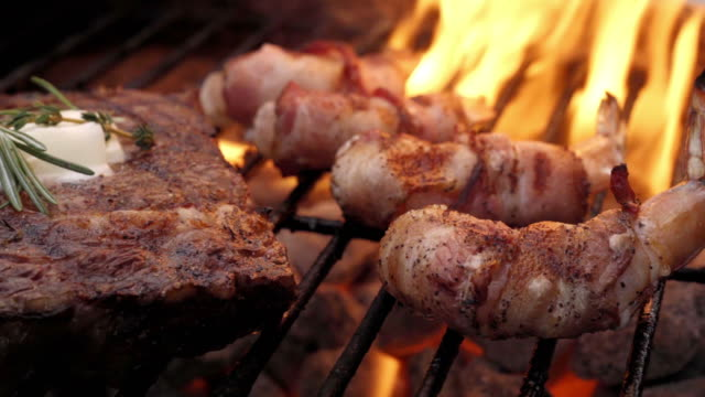 a video clip of grilled bacon wrapped shrimp and ribeye steak with flames - ketogenic diet stock videos & royalty-free footage