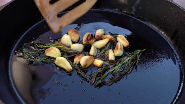 a video clip of rosemary and garlic cloves sauteed in a cast iron skillet - cast iron stock videos & royalty-free footage