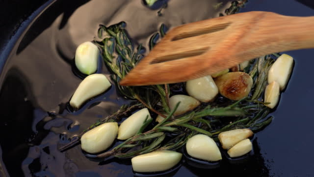 a video clip of rosemary and garlic cloves sauteed in a cast iron skillet with hot olive oil - ketogenic diet stock videos & royalty-free footage