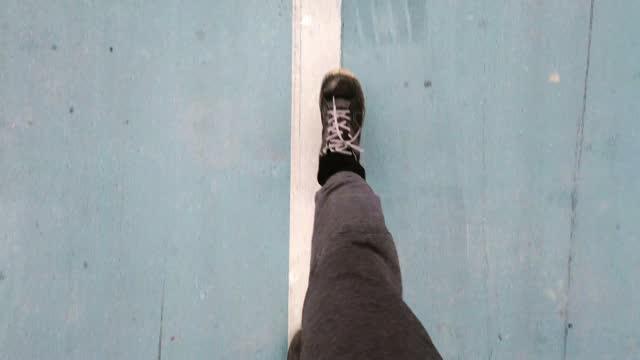vidéos et rushes de plan rapproché de vidéo vers le haut avec les pieds d'un homme marchant sur la route d'asphalte - vue du sol