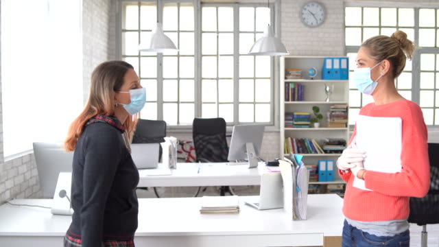 4k video colleagues in the office practicing alternative greeting for safety and protection during covid-19 - surgical mask stock videos & royalty-free footage