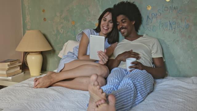 vídeos de stock, filmes e b-roll de vídeo-conferência na cama com a família - dispositivo de informação portátil