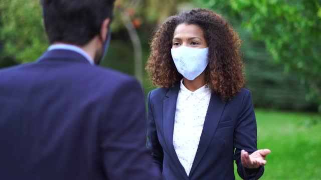 4k video couple coworkers wearing protective face mask on business travel arriving at the hotel - occurrence stock videos & royalty-free footage