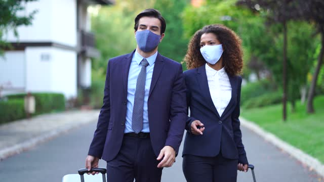 4k video couple coworkers wearing protective face mask on business travel arriving at the hotel - formal businesswear stock videos & royalty-free footage