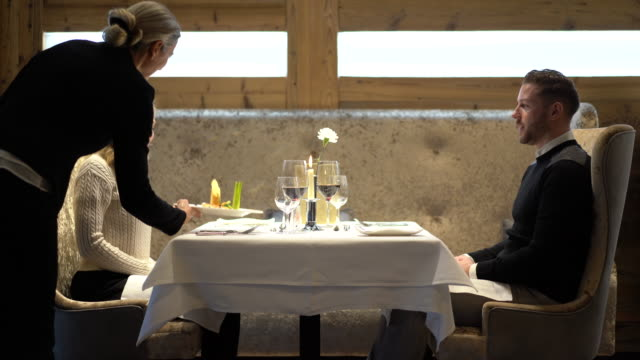 4k video couple dining out in luxury restaurant at table for two - dienstleistung stock-videos und b-roll-filmmaterial