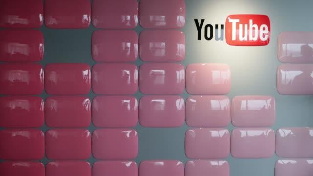 Video creators walk past Google Inc YouTube logo displayed at the company YouTube Space studio in Tokyo Japan Google's YouTube Space studio in Tokyo...