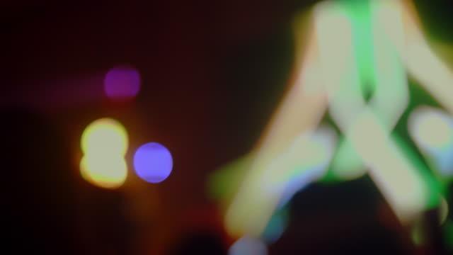 video defocus : tanzendes mädchen in einem nachtclub - arme hoch stock-videos und b-roll-filmmaterial