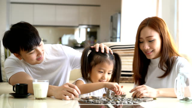 4K Video : Family saving money putting coins into glass bank