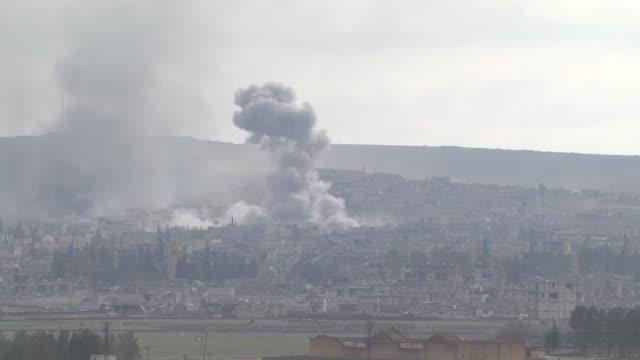 a video footage from suruc district of sanliurfa turkey near turkishsyrian border crossing shows smoke rising from the syrian border town of kobani... - 武力攻撃点の映像素材/bロール