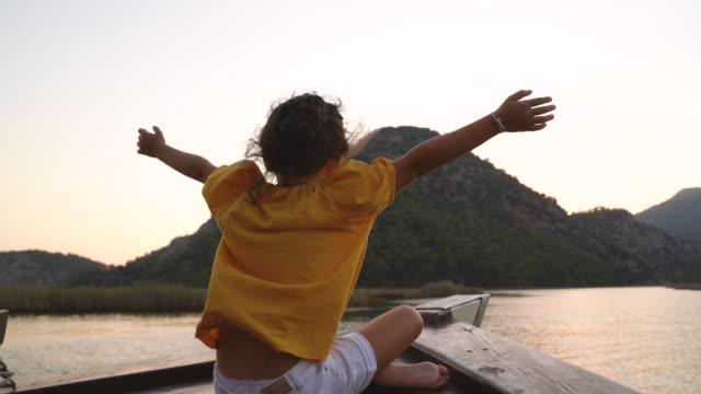 vídeos y material grabado en eventos de stock de imágenes de vídeo en 4k de una niña viajando en un velero al atardecer en dalyan, turquía - discovery