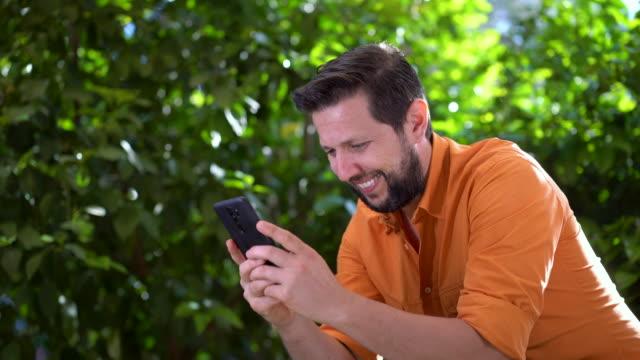4k videofilmer av en man som använder smart telefon och spela tv-spel - endast en ung man bildbanksvideor och videomaterial från bakom kulisserna