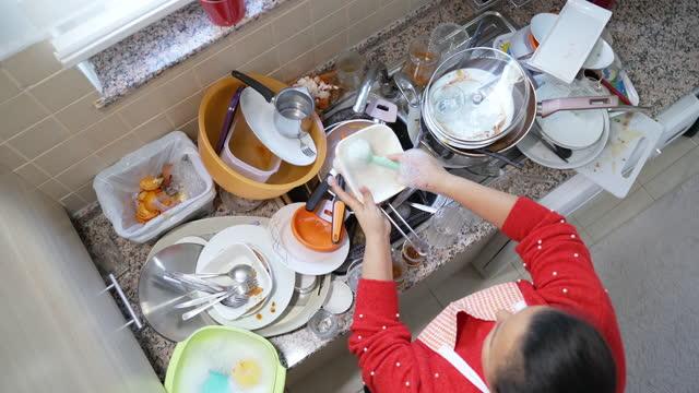 vidéos et rushes de 4k images vidéo d'une femme mature lavant la vaisselle au-dessus de l'évier à la maison - confusion