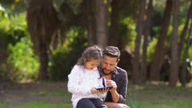 vídeos y material grabado en eventos de stock de 4k video de un joven padre e hija jugando con un teléfono inteligente en el parque - sms