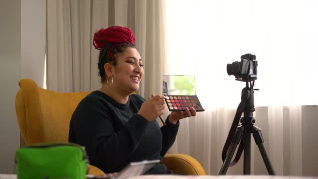 vidéos et rushes de 4k vidéo d'une jeune femme influenceur vlogging sur les cosmétiques de maquillage à la maison - blog vidéo