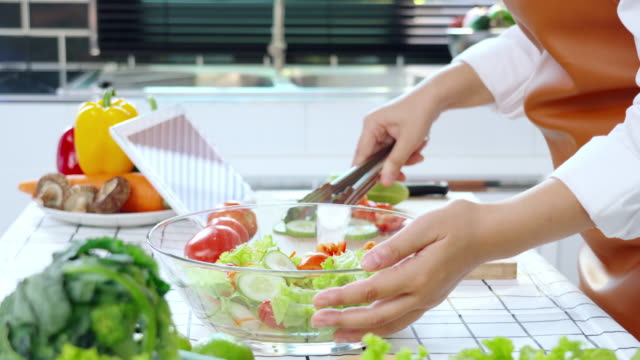 vídeos de stock e filmes b-roll de 4k video footage of asian woman cooking and making salad mixing vegetable and fruit in the kitchen at home - só mulheres jovens