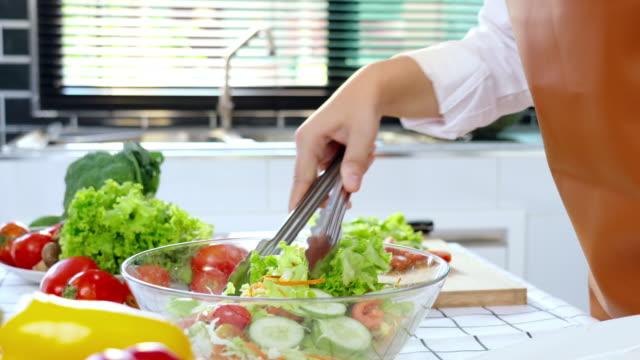 vídeos y material grabado en eventos de stock de imágenes de vídeo 4k de asian woman cocinando y haciendo ensalada mezclando verduras y frutas en la cocina en casa - sólo mujeres jóvenes