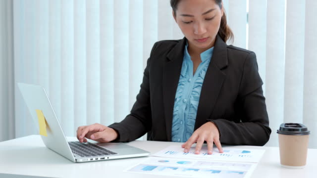 stockvideo's en b-roll-footage met 4k videobeelden van onderneemster die aan investeringsmarketingplan en financiële boekhoudingsgegevens met laptop in bureau werkt - rapport