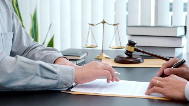 vidéos et rushes de séquences vidéo 4k d'avocat masculin consultant avec le client après l'accord de contrat dans le bureau - law
