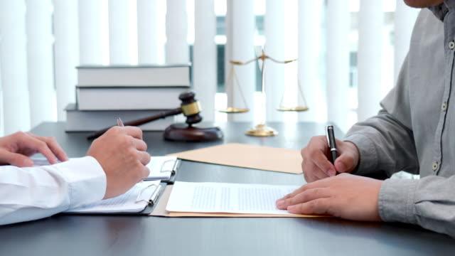 勤務契約締結後にクライアントと相談する男性弁護士の4kビデオ映像 - 裁判官点の映像素材/bロール