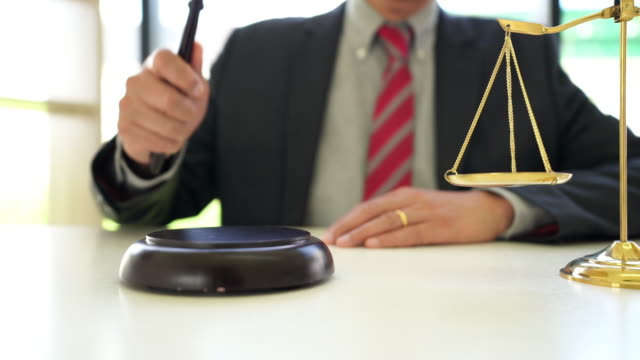 4k video footage of male lawyer holding knocking gavel in a lawyer's office - punishment stock videos & royalty-free footage