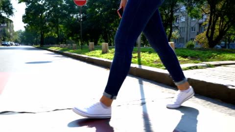 vidéos et rushes de séquences vidéo des jambes d'une femme traversant la rue. images anonymes. - trottoir