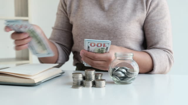 4k video footage of woman putting coins into money box, coins pile and counting banknotes to saving money planning to future - loan stock videos & royalty-free footage