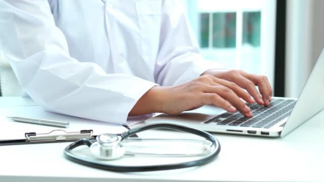 riprese video 4k di young asian doctor che lavora utilizzando un laptop in ospedale - dottoressa video stock e b–roll