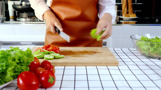 4k video footage of young asian woman being cutting and making salad mixing vegetable and fruit in the kitchen at home - chopping board stock videos & royalty-free footage