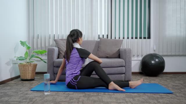 vidéos et rushes de séquences vidéo 4k de jeune femme asiatique faisant le yoga travaillant dehors des exercices à la maison - quête de beauté