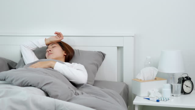 vídeos de stock e filmes b-roll de 4k video footage of young asian woman suffering with the flu and feeling sick in bedroom at home - só mulheres jovens