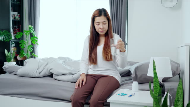 vídeos de stock e filmes b-roll de 4k video footage of young asian woman taking medicine suffering with the flu and feeling sick in bedroom at home - só mulheres jovens
