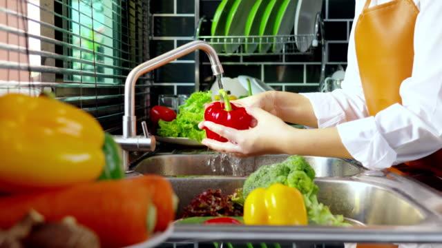 vídeos de stock e filmes b-roll de 4k video footage of young asian woman washing bell pepper for preparing cooking food - lava loiças