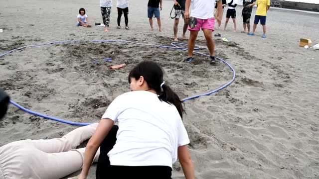 video footage shows men, women and children testing their strength against each other in a sumo wrestling contest on a sandy beach in konan, kochi... - レスリング点の映像素材/bロール