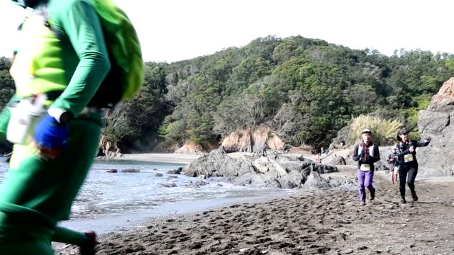 video footage shows participants running through coastal rocks to reach the finish line of the 11th senba coastal cliff trail running race held on... - 手を伸ばす点の映像素材/bロール