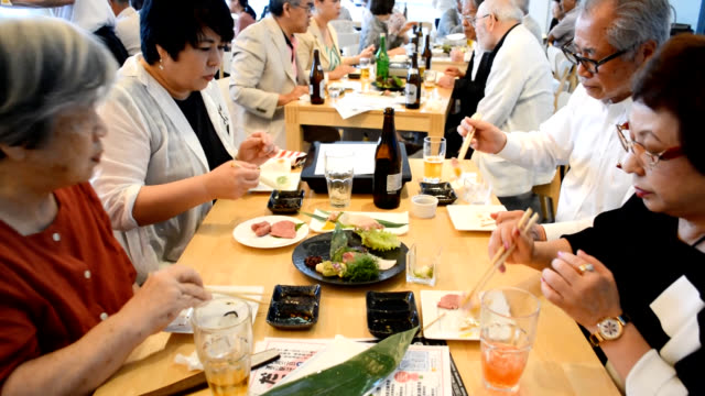 stockvideo's en b-roll-footage met video footage shows people feasting on whale meat dishes at an aquarium in shimonoseki yamaguchi prefecture a city that serves as a base for whaling... - cetacea